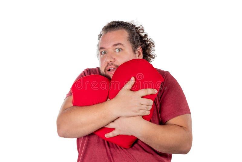 Un tir de studio d'un gros homme jugeant un oreiller en forme de coeur rouge d'isolement sur le fond blanc photographie stock libre de droits
