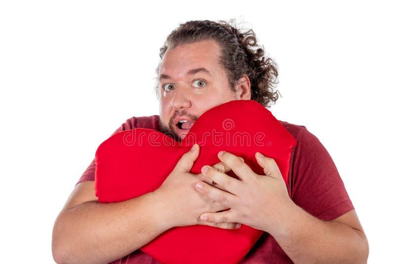 Un tir de studio d'un gros homme jugeant un oreiller en forme de coeur rouge d'isolement sur le fond blanc images libres de droits