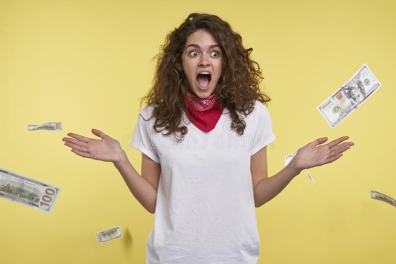 Un tir de studio de la femme qui gagne beaucoup d'argent, argent liquide tombant sur sa tête, d'isolement au-dessus du fond jaune photo stock