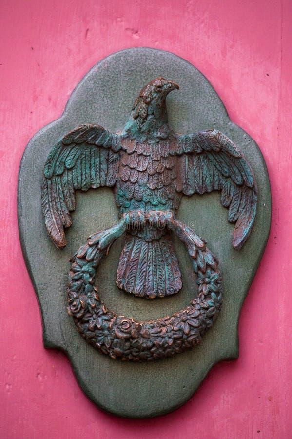 Un tirador de puerta de bronce decorativo del viejo estilo en una puerta roja de madera, la característica distintiva y el símbol fotografía de archivo