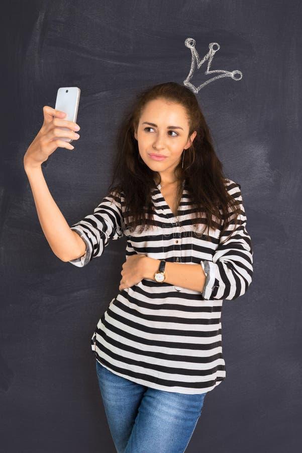 Un tiro de la mujer joven atractiva que se coloca delante de la pizarra imágenes de archivo libres de regalías