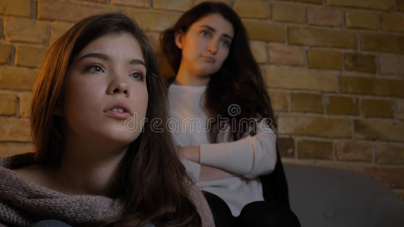 Un tiro del primo piano di due giovani ragazze sveglie che guardano insieme TV e che spendono insieme tempo mentre riposando sull immagini stock