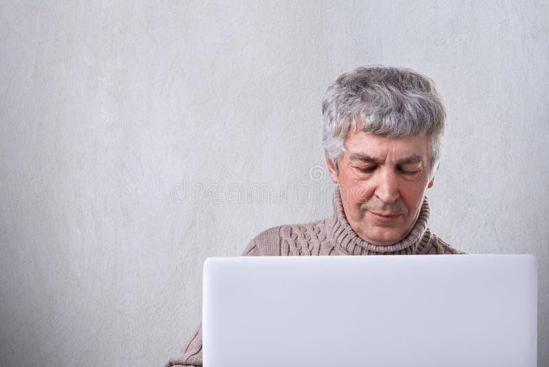 Un tiro del varón mayor que tiene pelo y wtinkles grises en la cara que mira en la pantalla de su ordenador portátil que lee un l fotografía de archivo libre de regalías