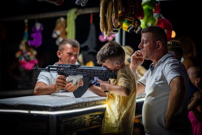 Un tiroteo joven del muchacho y del padre con el arma automática del airsoft en una feria foto de archivo