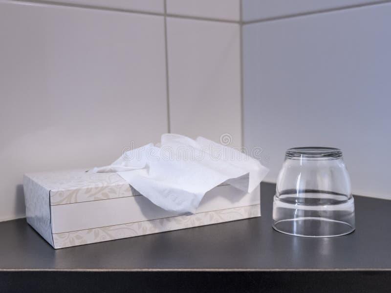 Un tissuebox y un vidrio foto de archivo