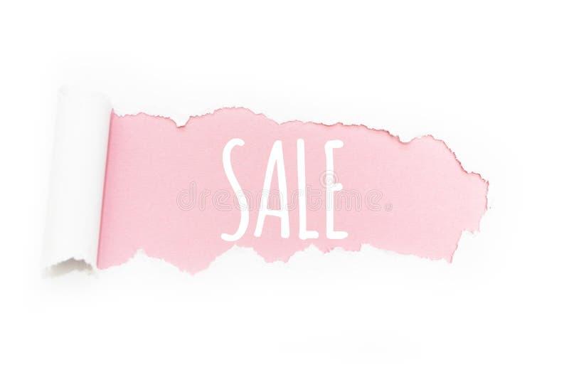 """Un titolo """"vendita """"nella rottura di carta su un fondo rosa immagini stock libere da diritti"""