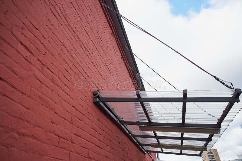 Un toldo hecho del policarbonato en un con base metálica montada en una pared de ladrillo roja foto de archivo