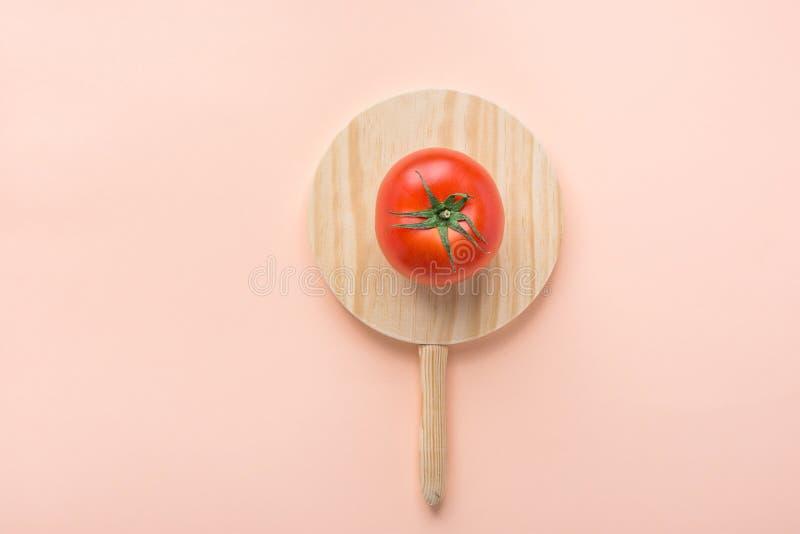 Un tomate orgánico maduro con las hojas del verde en tabla de cortar de madera redonda en fondo rosado Flámula de la bandera del  imagenes de archivo