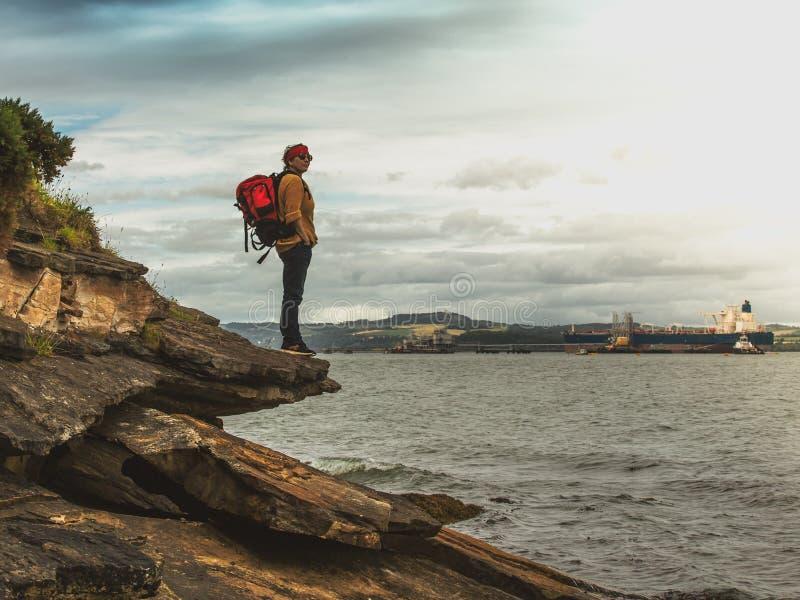 Un touriste féminin, se tenant sur les roches et regardant la rivière photo libre de droits