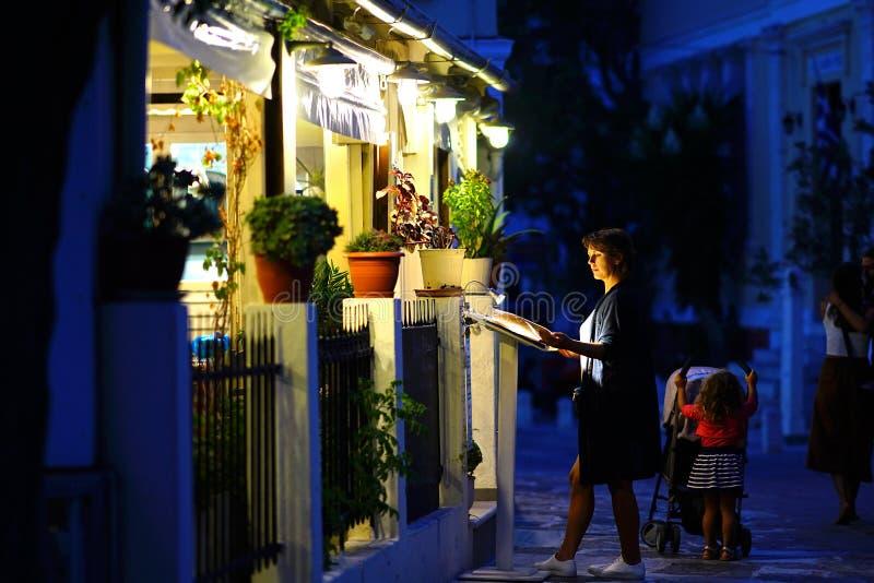 Un touriste regarde le menu d'un restaurant dans Lefkes, île de Paros photos stock