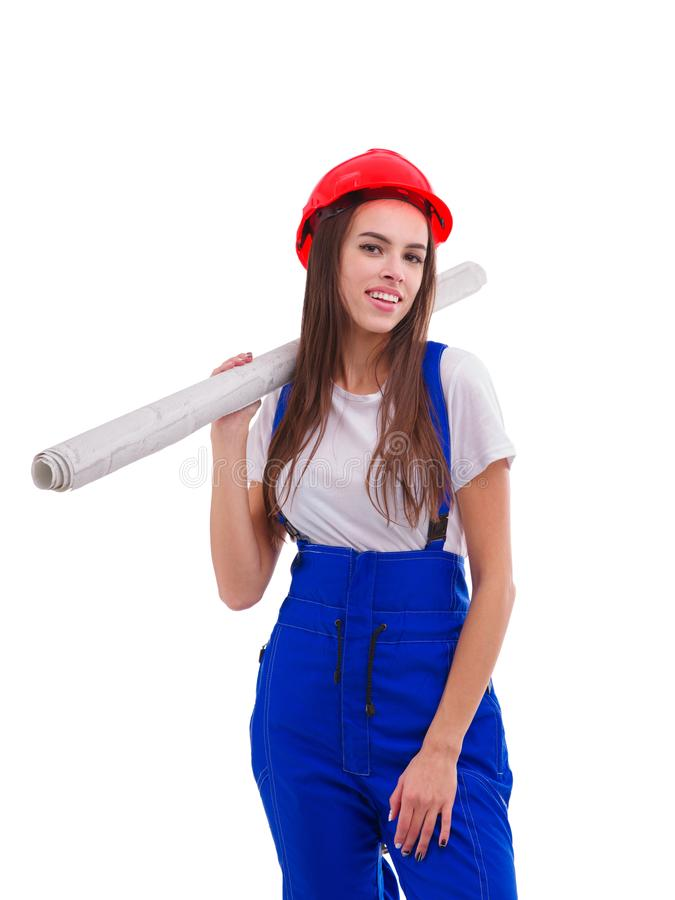 Un trabajador agradable de la muchacha, llevando un uniforme y un casco, llevando a cabo un rollo del papel pintado en su hombro  imagen de archivo