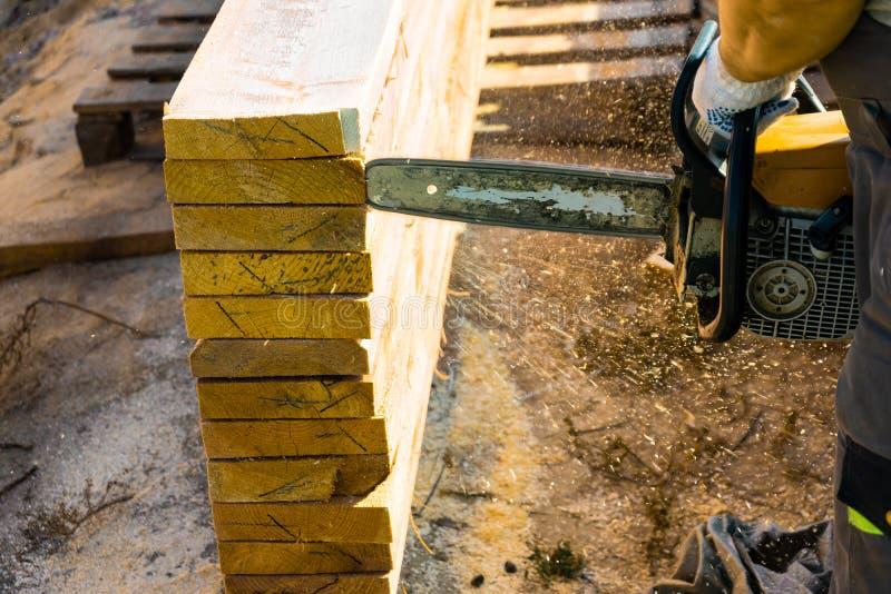 Un trabajador asierra de un tablero de madera de la motosierra Construcción de la casa imágenes de archivo libres de regalías