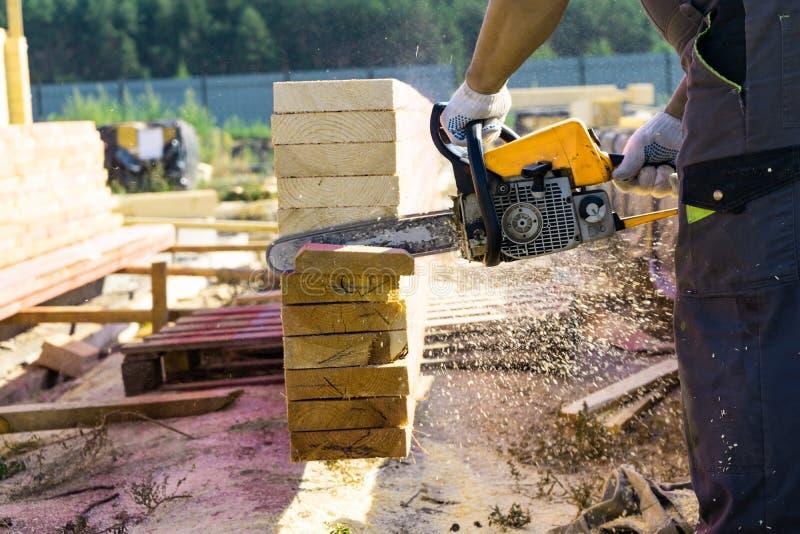 Un trabajador asierra de un tablero de madera de la motosierra Construcción de la casa fotografía de archivo