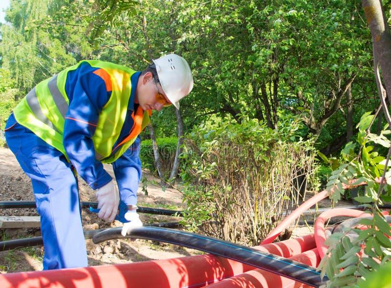 Un trabajador con casco blanco y chaleco amarillo corta una tubería de plástico con tijeras azules imágenes de archivo libres de regalías
