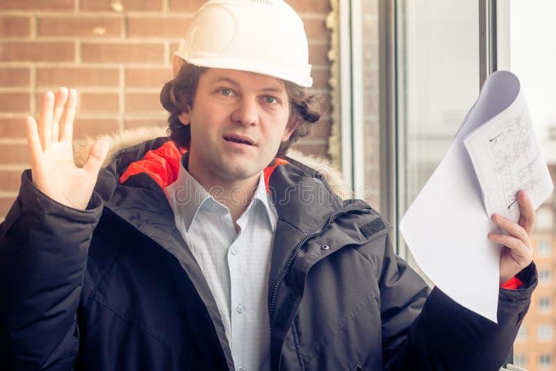 Un trabajador contrariedad enojado del constructor en un casco con los dibujos del proyecto planea en su una mano y teléfono móvi imágenes de archivo libres de regalías