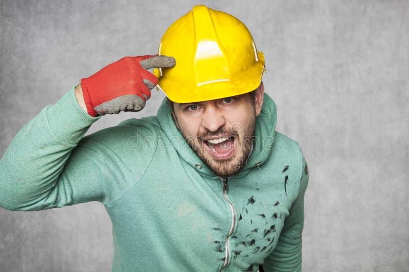 Un trabajador contrariedad enojado que mira a escondidas en un casco protector fotos de archivo libres de regalías
