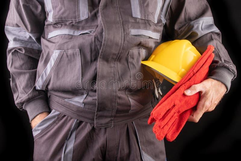 Un trabajador de producci?n en workwear con un casco protector en su mano Workwear especial para los empleados imagen de archivo