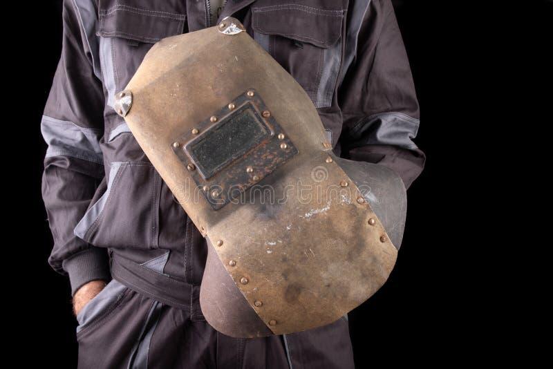 Un trabajador de producci?n en workwear con una m?scara de soldadura a disposici?n Workwear especial para los empleados fotos de archivo libres de regalías