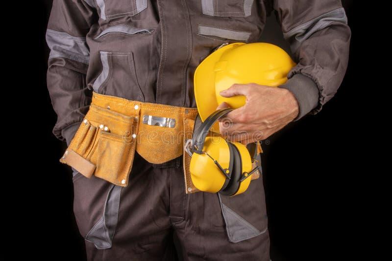 Un trabajador de producci?n en workwear con un casco protector en su mano Workwear especial para los empleados imágenes de archivo libres de regalías