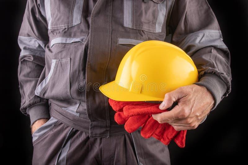 Un trabajador de producci?n en workwear con un casco protector en su mano Workwear especial para los empleados foto de archivo libre de regalías