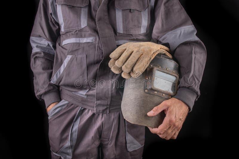 Un trabajador de producci?n en workwear con una m?scara de soldadura a disposici?n Workwear especial para los empleados foto de archivo