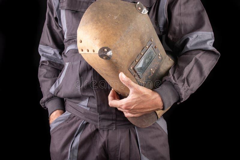 Un trabajador de producci?n en workwear con una m?scara de soldadura a disposici?n Workwear especial para los empleados imágenes de archivo libres de regalías
