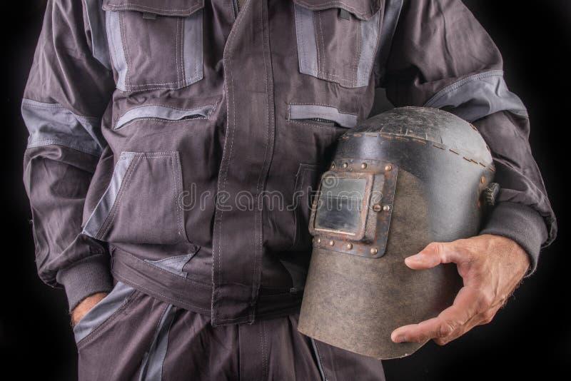 Un trabajador de producci?n en workwear con una m?scara de soldadura a disposici?n Workwear especial para los empleados imagenes de archivo