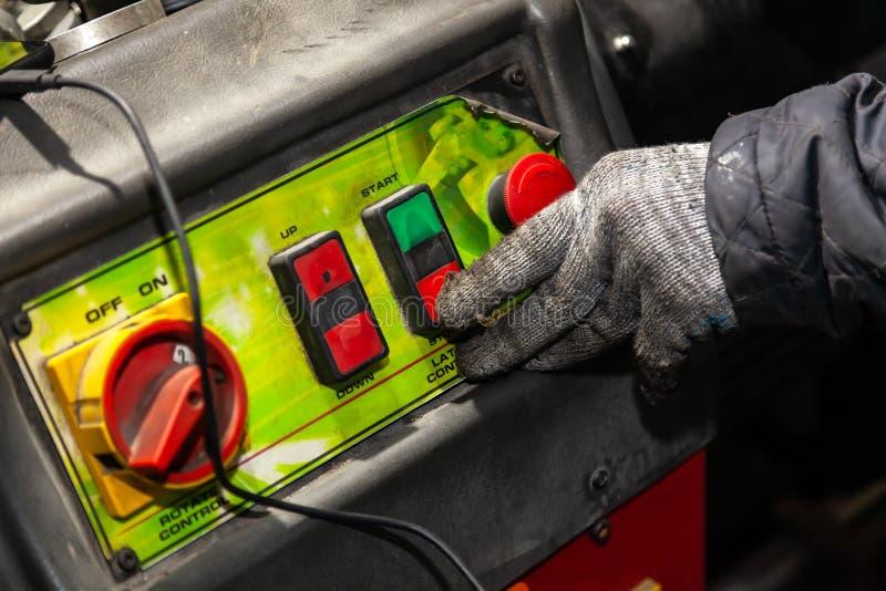 Un trabajador de sexo masculino en guantes de trabajo presiona el botón rojo en el panel de control de la máquina en un taller o  imagen de archivo libre de regalías
