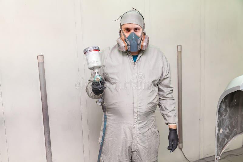 Un trabajador de sexo masculino que pinta un coche se está colocando en una cabina de espray en ropa protectora con un arma de es imagenes de archivo