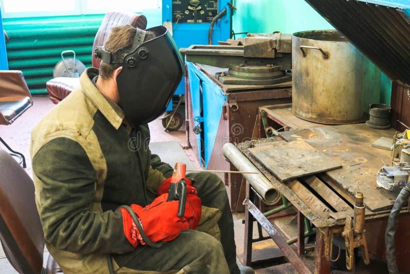 Un trabajador de sexo masculino un soldador en una máscara protectora suelda con autógena un tubo del metal en una estación de la fotos de archivo