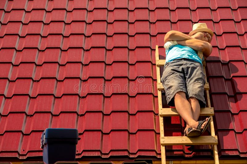 un trabajador dormido durante una rotura que toma el sol en las escaleras en el tejado imagen de archivo