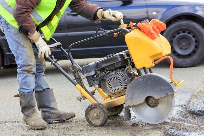 Un trabajador en un chaleco reflexivo verde corta un pedazo de mún asfalto con un cortador de la gasolina en la calzada imagen de archivo
