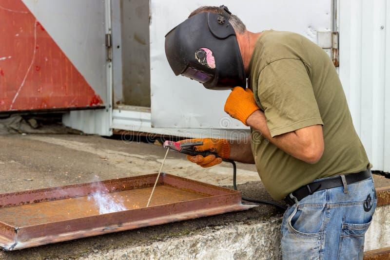 Un trabajador en una máscara de soldadura realiza el trabajo de soldadura sobre el metal Partes en enlace de metal bajo temperatu imagenes de archivo