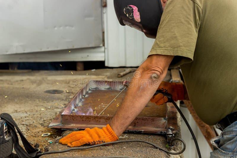 Un trabajador en una máscara de soldadura realiza el trabajo de soldadura sobre el metal Partes en enlace de metal bajo temperatu fotografía de archivo