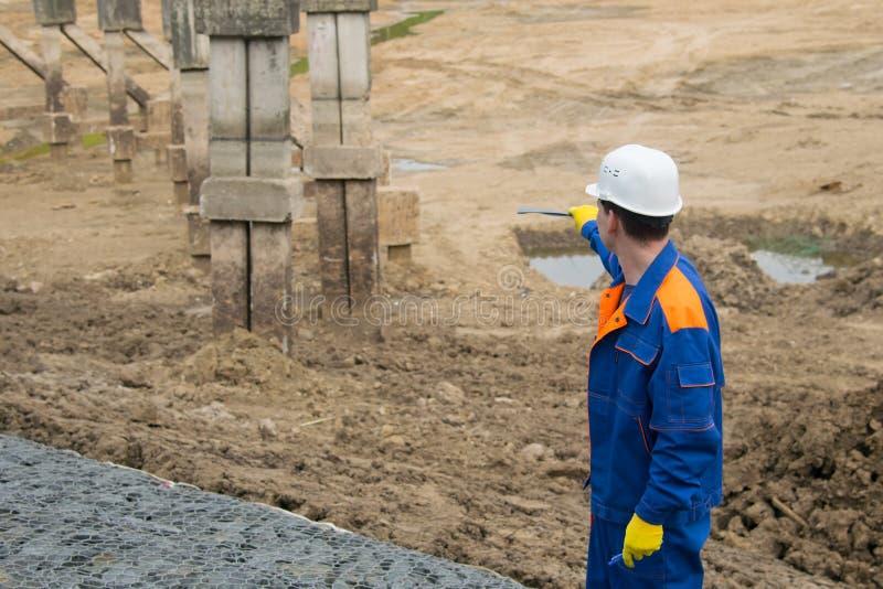 Un trabajador en un uniforme azul y un casco blanco muestra el desarrollador en la etapa de la construcción de la fundación para  fotografía de archivo