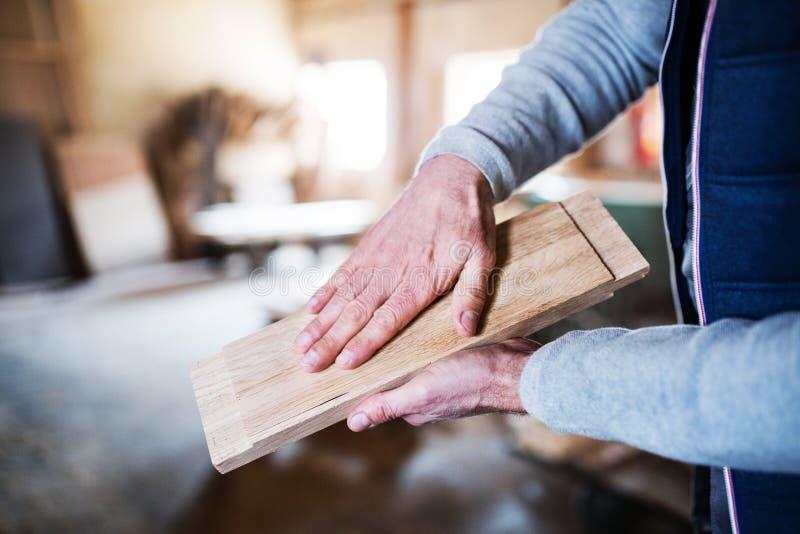 Un trabajador irreconocible del hombre en el taller de la carpintería, trabajando con madera foto de archivo
