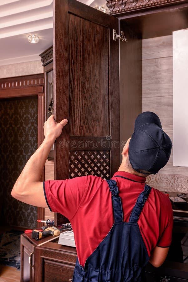 Un trabajador joven est? montando los muebles de madera modernos de la cocina fotografía de archivo