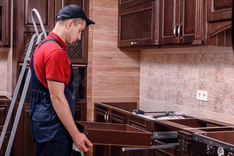 Un trabajador joven instala un cajón Instalación de los muebles de madera modernos de la cocina imagen de archivo libre de regalías