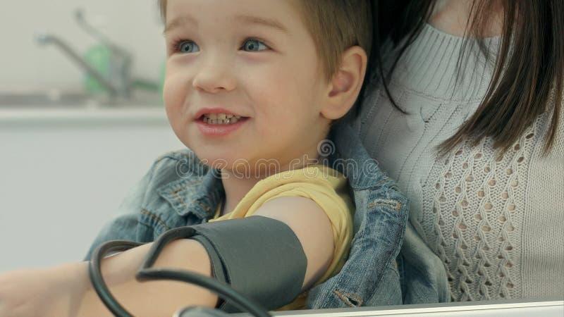 Un trabajador médico que toma a un ` joven s del muchacho la presión arterial imágenes de archivo libres de regalías