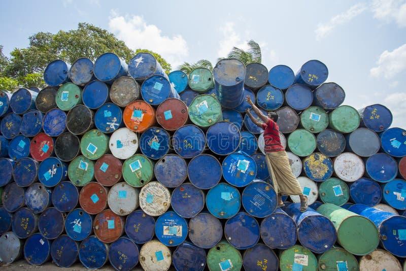 Un trabajador organiza los barriles en las áreas de Sadarghat de los ríos de Karnafuli, Chittagong, Bangladesh fotos de archivo