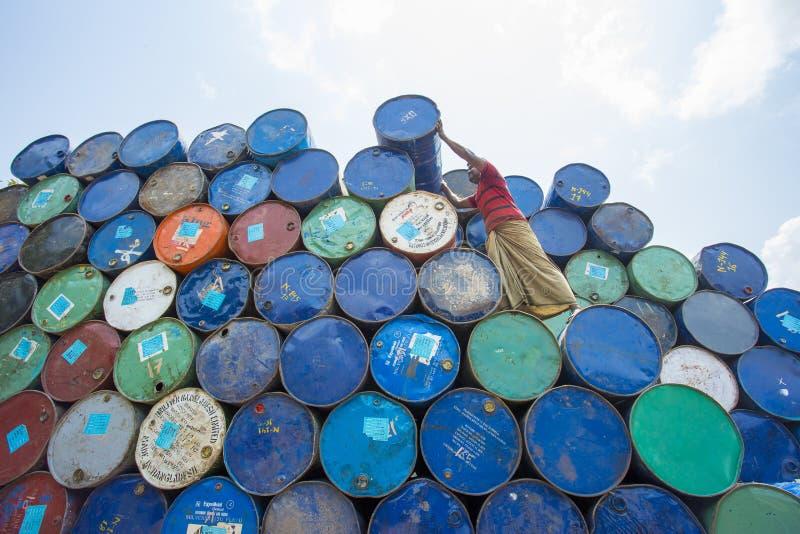 Un trabajador organiza los barriles en las áreas de Sadarghat de los ríos de Karnafuli, Chittagong, Bangladesh fotografía de archivo