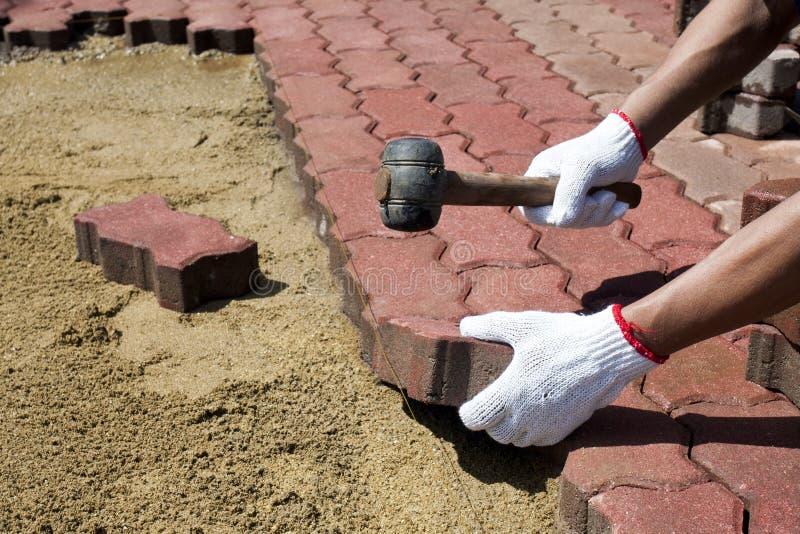 Un trabajador que pone bloques de pavimentación concretos. foto de archivo