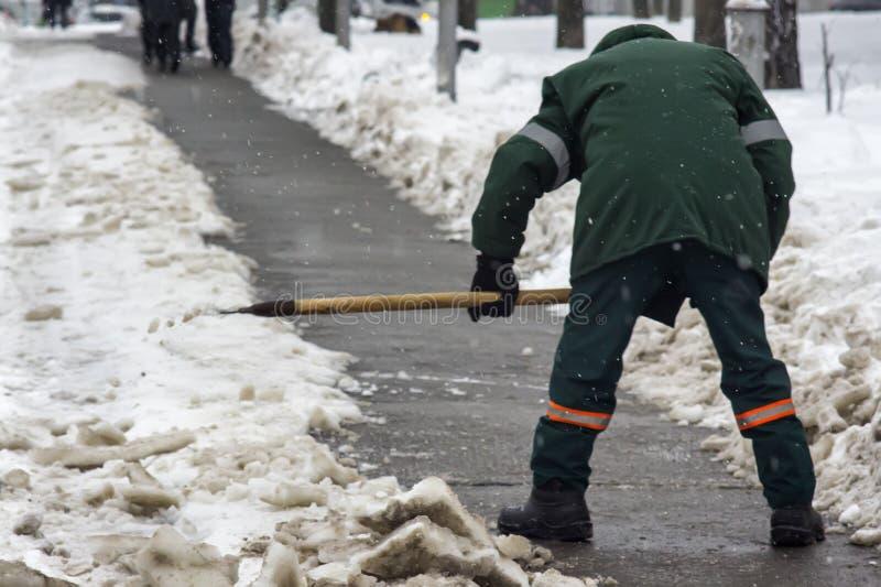 Un trabajador quita nieve del camino en el invierno frío imágenes de archivo libres de regalías