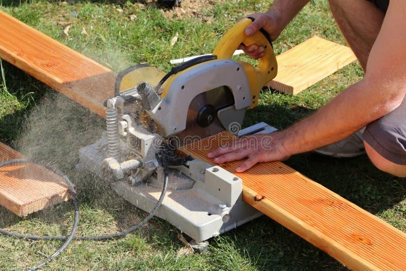 Un trabajador vio que la madera con una tajada vio imagenes de archivo