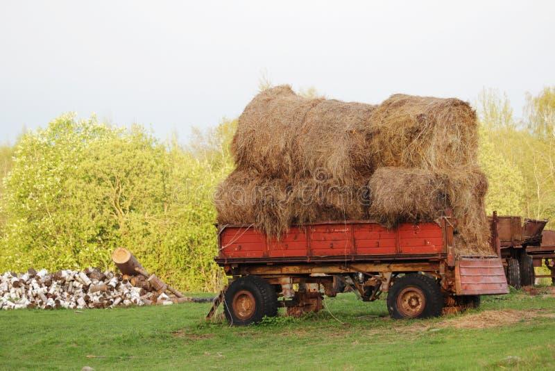 Un tracteur avec des balles de foin dans la campagne russe image stock