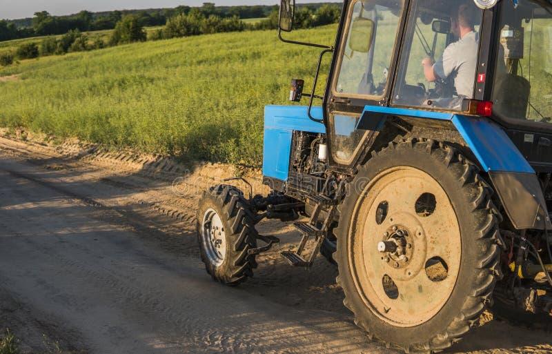 Un tracteur bleu avec une remorque pour des tours de travaux agricoles le long d'une route dans un domaine de blé photo libre de droits