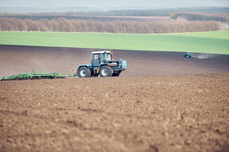 Un tracteur labourant et semant sur le terrain photos stock