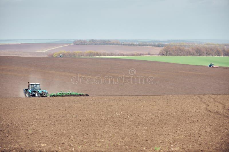 Un tracteur labourant et semant sur le terrain image libre de droits