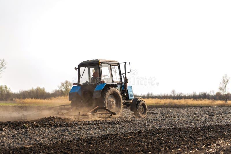 Un tracteur laboure un champ pour semer des cultures images libres de droits