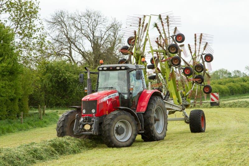 Un tractor de granja con el rastrillo de la nómina listo para hacer ensilaje fotografía de archivo